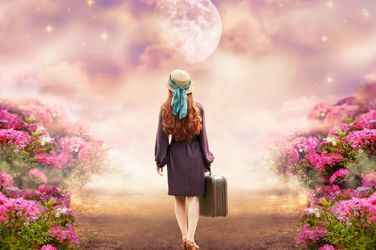 Girl with a suitcase looking at the Moon